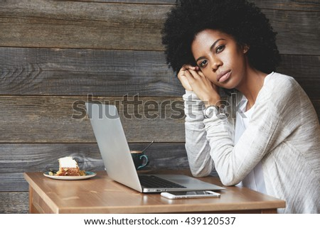 People and lifestyle concept. Beautiful African woman with Afro haircut wearing stylish clothes, looking at the camera with serious expression, leaning her elbows on the table with laptop and phone - stock photo