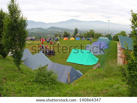people and tents in a scout camp open air in the middle of nature - stock photo