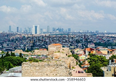 People are admiring view over istanbul from the top of city wall ruins - stock photo