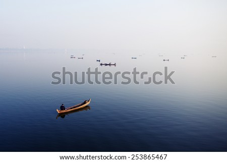 People are fishing on the boat at the Taungthaman lake, near by U bein bridge,the oldest and longest teak wooden bridge in the world, Amarapura, Myanmar. - stock photo