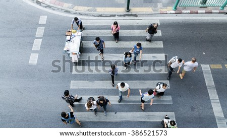 People are moving across the crosswalk on the city road (on top view) - stock photo