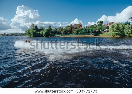 People are rushing along the lake on a water bike, leaving behind a column of spray and foam - stock photo