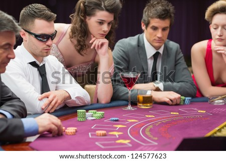 People around the poker table in casino - stock photo