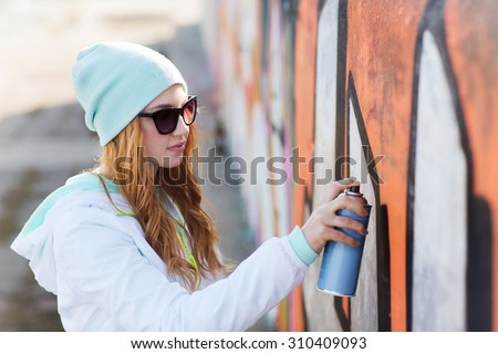 people, art, creativity and youth culture concept - young woman or teenage girl drawing graffiti with spray paint on street wall - stock photo