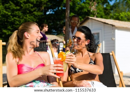 People at beach drinking having a party, two girls clinking glasses with cocktails having fun - stock photo