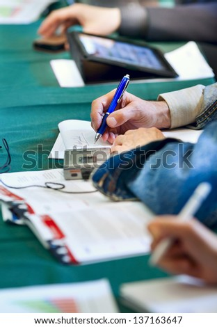 People at business conference are at the table writing in notebook - stock photo