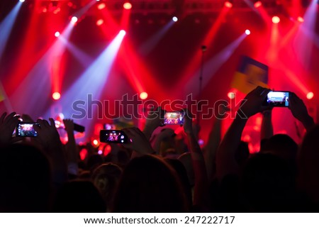 People at concert shooting video or photo. - stock photo