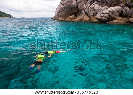 people at snorkeling in the tropical water , similan Island , phuket Island in thailand - stock photo
