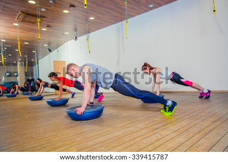 People at the health club with personal trainer, learning the correct form. Fitness group training with bosu at the gym. - stock photo