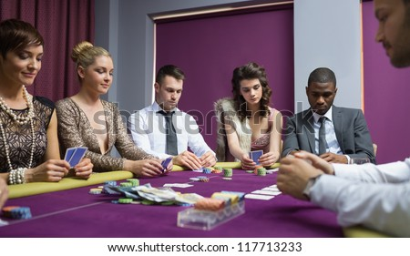 People at the poker table in casino - stock photo