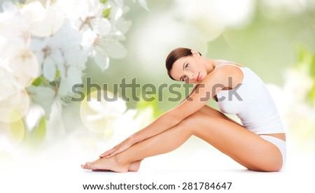 people, beauty and body care concept - beautiful woman in cotton underwear touching legs over green natural cherry blossom background - stock photo