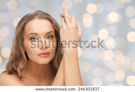 people, beauty, body and skin care concept - beautiful woman face and hands over holidays lights background - stock photo