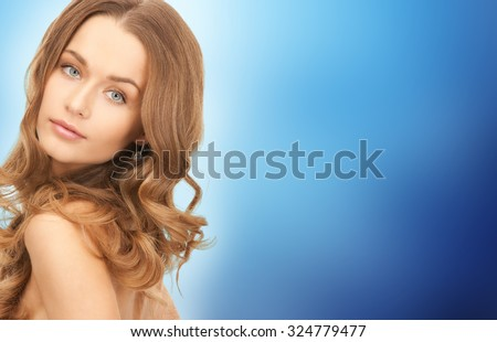 people, beauty, hair and skin care concept - beautiful woman with curly hairstyle over blue background - stock photo