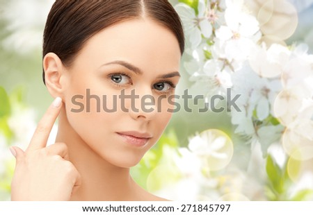 people, beauty, hearing and healthcare concept - face of beautiful woman touching her ear over green blooming garden background - stock photo