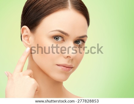 people, beauty, hearing and healthcare concept - face of beautiful woman touching her ear over green background - stock photo