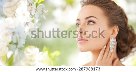 people, beauty, jewelry and accessories concept - beautiful woman with diamond earrings over summer garden and cherry blossom background - stock photo