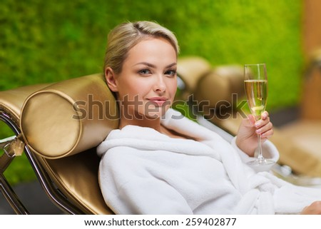 people, beauty, lifestyle, holidays and relaxation concept - beautiful young woman in white bath robe lying on chaise-longue and drinking champagne at spa - stock photo