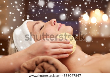 people, beauty, spa, cosmetology and relaxation concept - close up of beautiful young woman lying with closed eyes having face cleaning by sponge and beautician hand in spa salon with snow effect - stock photo