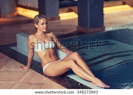 people, beauty, spa, healthy lifestyle and relaxation concept - beautiful young woman in bikini swimsuit sitting on swimming pool edge - stock photo