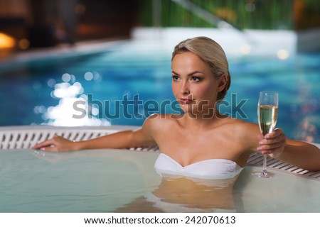 people, beauty, spa, healthy lifestyle and relaxation concept - beautiful young woman wearing bikini swimsuit sitting with glass of champagne in jacuzzi at poolside - stock photo
