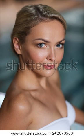 people, beauty, spa, healthy lifestyle and relaxation concept - close up of beautiful young woman in swimsuit at swimming pool - stock photo