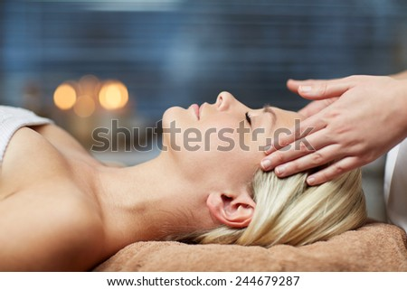 people, beauty, spa, healthy lifestyle and relaxation concept - close up of beautiful young woman lying with closed eyes and having face or head massage in spa - stock photo