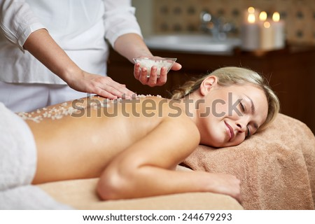 people, beauty, spa, massage and relaxation concept - close up of beautiful young woman lying with closed eyes and therapist holding salt bowl in spa - stock photo