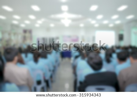 People blur listening for lecture speech in large convention room - stock photo