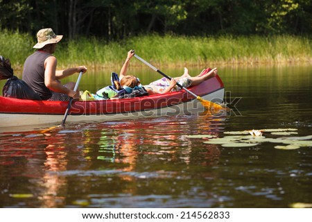 People boating on small river full of water lilies and having fun - stock photo