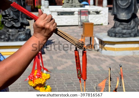 People burning incense and red candle for pray god at Suphanburi city pillar shrine in Suphanburi, Thailand. - stock photo