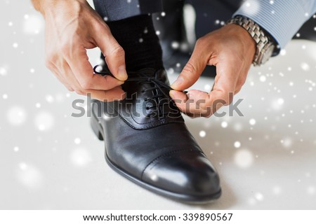 people, business, fashion and footwear concept - close up of man leg and hands tying shoe laces over snow effect - stock photo