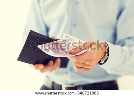 people, business, finances and money concept - close up of businessman hands holding open wallet with euro cash - stock photo