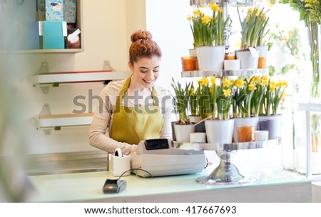 people, business, sale and floristry and concept - happy smiling florist woman at flower shop cashbox on counter - stock photo