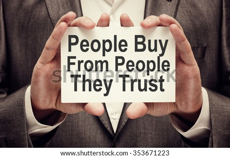 People Buy From People They Trust. Businessman holding a card with a message text written on it - stock photo