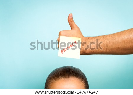 "People care about privacy. Hand making ""thumb up"" gesture with a stick note privacy. The hand is over top of head of woman. - stock photo"