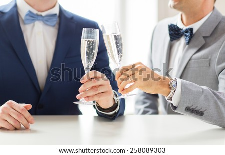people, celebration, homosexuality, same-sex marriage and love concept - close up of happy married male gay couple in suits and bow-ties drinking sparkling wine and clinking glasses on wedding - stock photo
