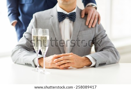 people, celebration, homosexuality, same-sex marriage and love concept - close up of happy married male gay couple in suits and bow-ties with sparkling wine glasses putting hand on shoulder on wedding - stock photo