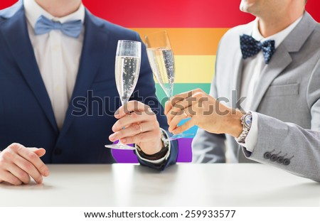 people, celebration, homosexuality, same-sex marriage and love concept - close up of happy married male gay couple drinking sparkling wine and clinking glasses on wedding over rainbow flag background - stock photo