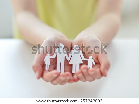 people, charity and care concept - close up of child hands holding paper family cutout at home - stock photo