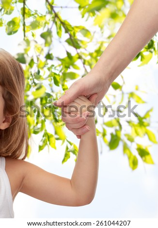 people, charity, family and adoption concept - close up of woman and little girl holding hands over green tree leavers background - stock photo
