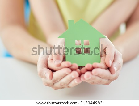 people, charity, family and home concept - close up of woman and girl holding green paper house cutout in cupped hands - stock photo