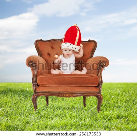 people, childhood and royalty concept - happy baby boy in royal hat with lollipop sitting on chair over blue sky and grass background - stock photo