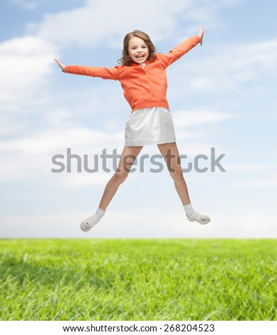 people, childhood, happiness, motion and summer concept - happy girl in casual clothes jumping high over blue sky and grass background - stock photo