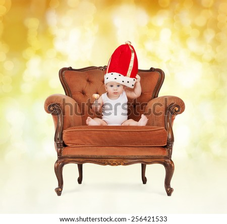 people, childhood, holidays and royalty concept - happy baby boy in royal hat with lollipop sitting on chair over yellow lights background - stock photo