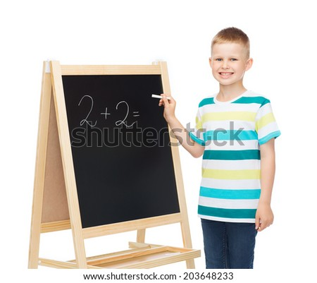 people, childhood, mathematics and education concept - happy little boy with blackboard and chalk writing math exercise - stock photo