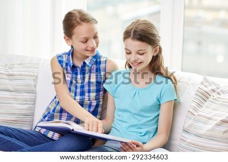 people, children, friends, literature and friendship concept - two happy girls sitting on sofa and reading book at home - stock photo