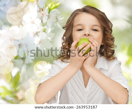 people, children, healthy eating, ecology and food concept- happy girl eating green apple over summer or spring garden background - stock photo