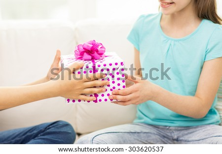 people, children, holidays, friends and friendship concept - close up of happy little girls with birthday present sitting on sofa at home - stock photo