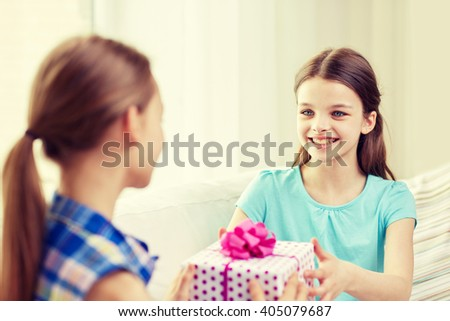 people, children, holidays, friends and friendship concept - happy little girls with birthday present sitting on sofa at home - stock photo