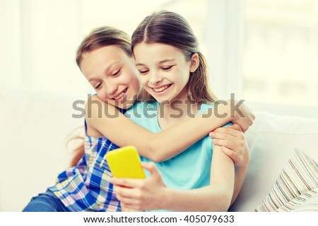 people, children, technology, friends and friendship concept - happy little girls sitting on sofa and taking selfie with smartphone and hugging at home - stock photo